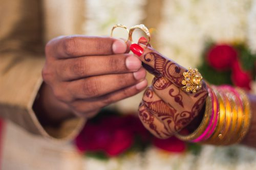 Groom and Bride holding their wedding rings